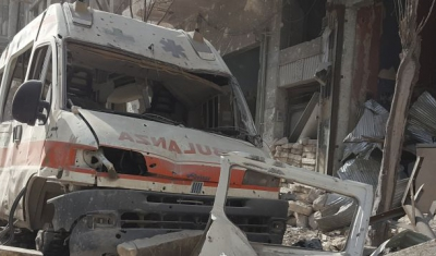 Syria, Aleppo, Al-Kallaseh district. The remains of an ambulance in the debris.