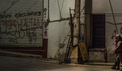 Mexico, two persons walk in th street at night