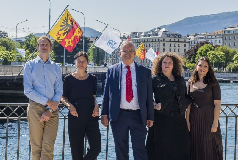The team of the platform in front of the flags of the Geneva Human Rights Platform on the Mont-Blanc Bridge