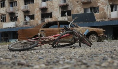 Ukraine, damaged bicycle and car in front of a destroyed building