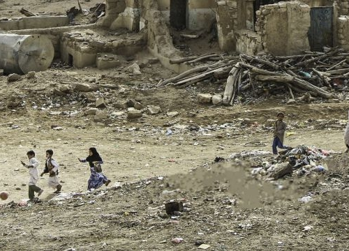 Yemen, Saada. A group of children play football against a backdrop of destroyed houses. The northern governorate has witnessed several episodes of violence since 2006 that left behind immense destruction.