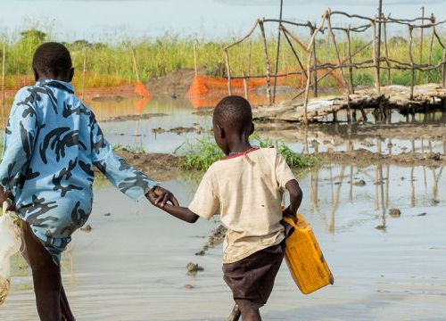 Bentiu, South Sudan, two boys walk in a river