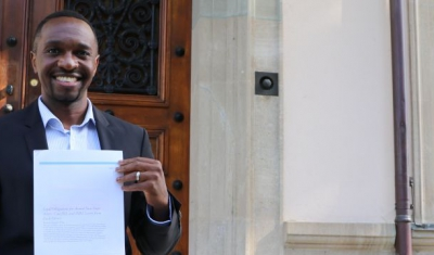 Joshua Niyo holding his paper in front of the Geneva Academy