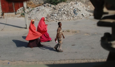 Women in bright headscarves walk along Mogadishu street