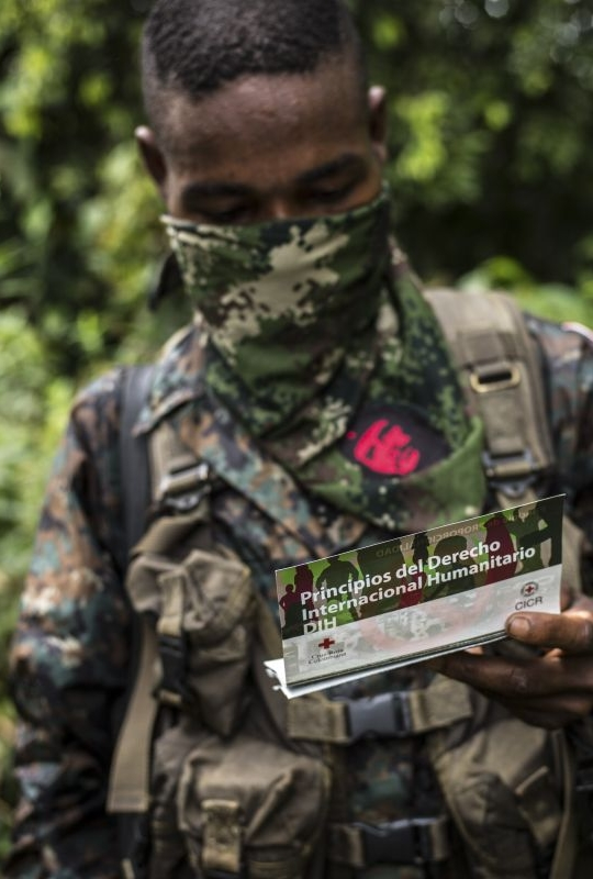 Member of an armed groupo holding an ICRC leaflet on IHL