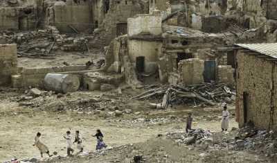Yemen, Saada. A group of children play football against a backdrop of destroyed houses.