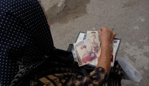 Azerbaijan, Shamkir. A mother looks through photographs of her missing son.